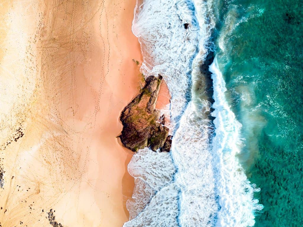 Aerial photo of sand and waves from a drone