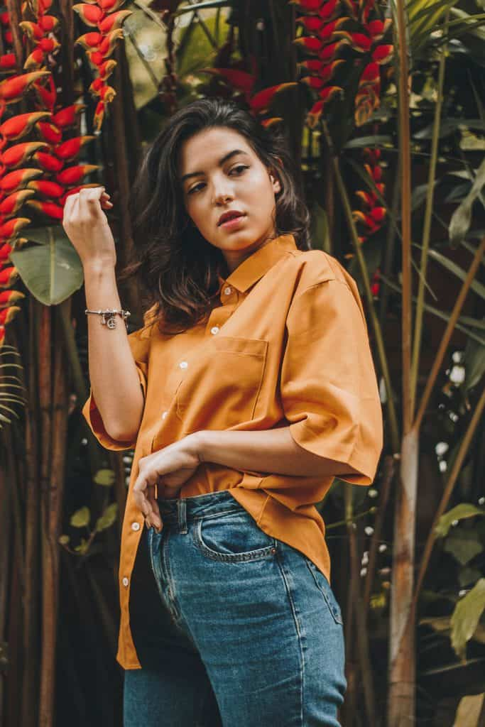 girl with orange shirt and flowers on the background